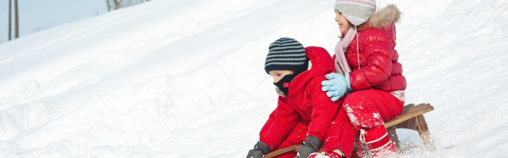 Two little kids - boy and girl - sliding with sledge in the snow